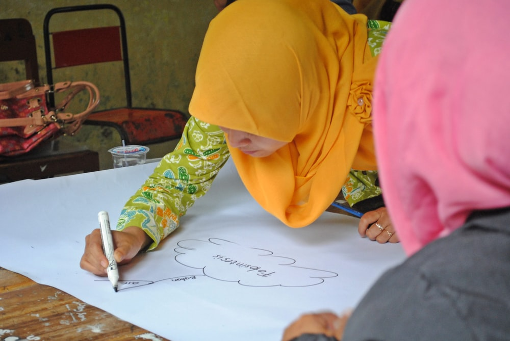 person in yellow hijab writing on white paper
