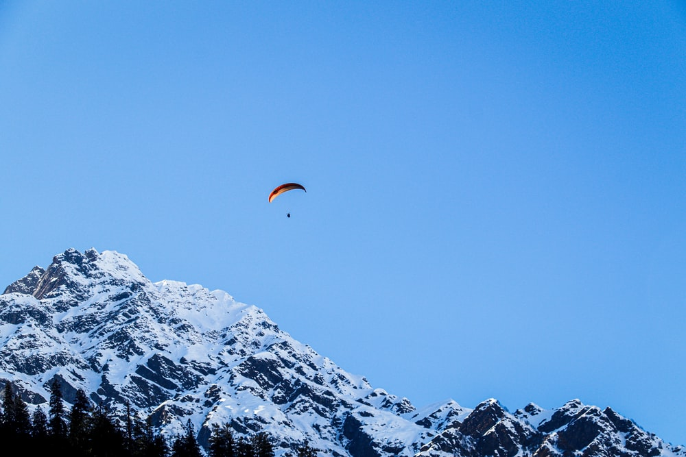 person in orange parachute over snow covered mountain during daytime