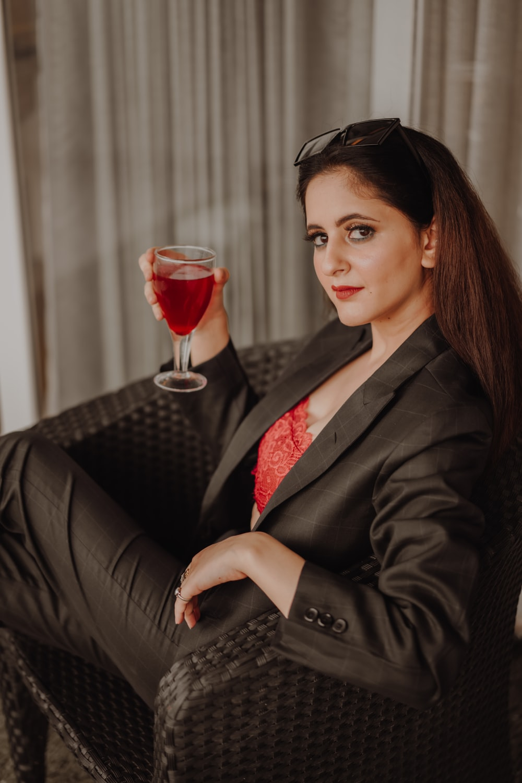 woman in black blazer holding wine glass