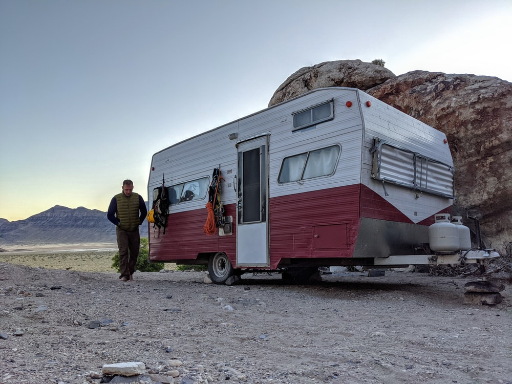 man in black jacket standing beside white and brown rv trailer during daytime