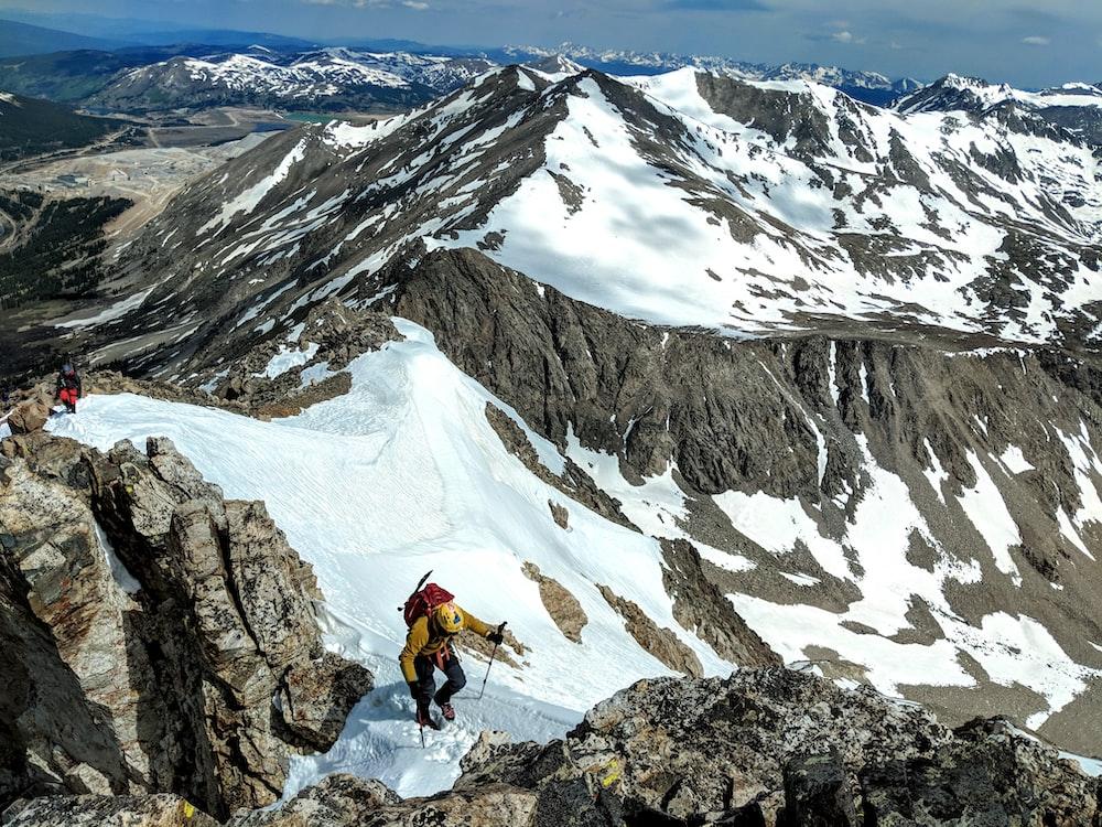 man in orange jacket and black pants standing on rock mountain during daytime