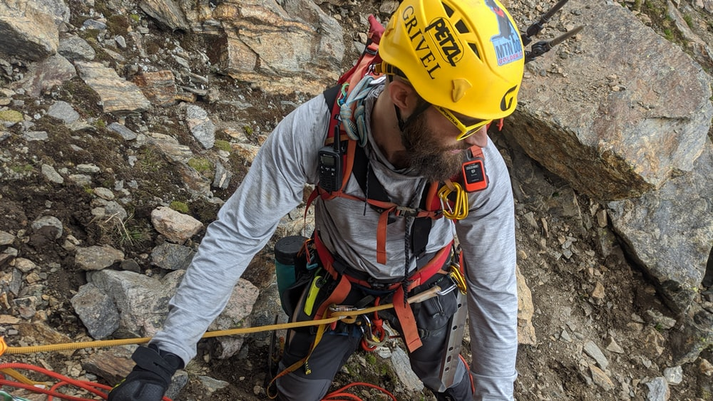 man in yellow hard hat and yellow helmet climbing on rocky mountain during daytime