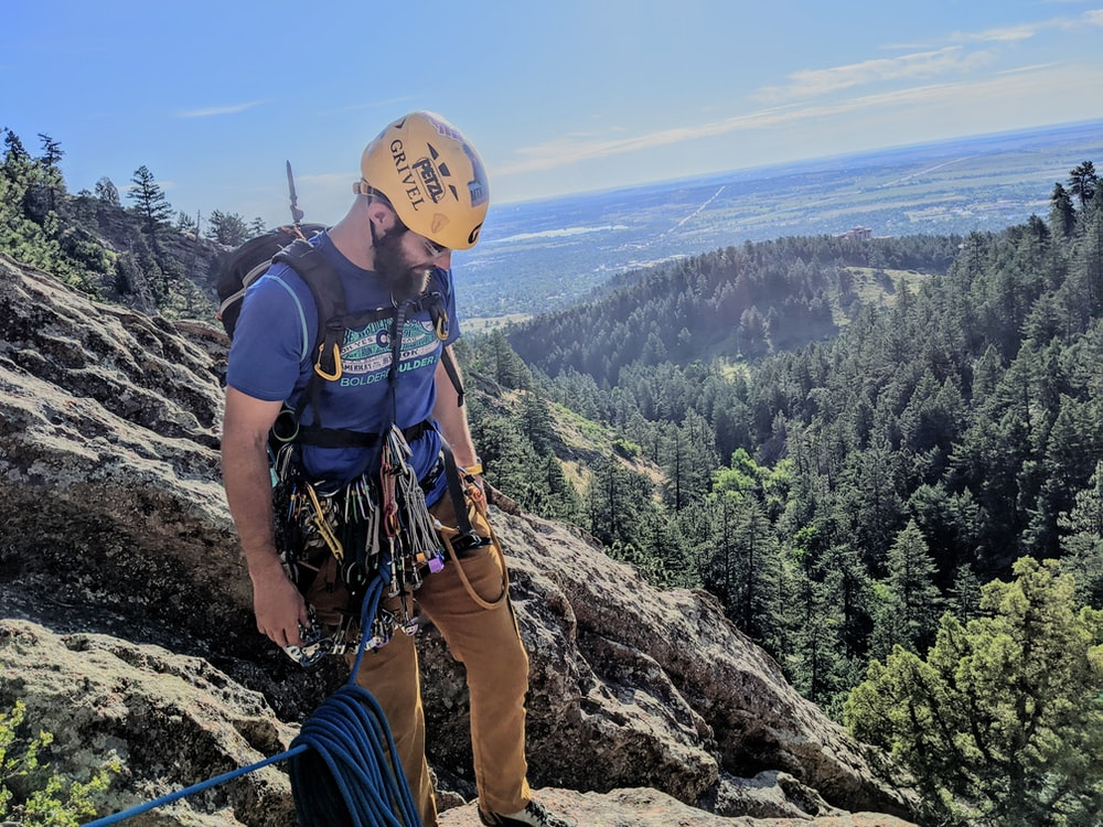 man in black t-shirt and blue pants with brown backpack standing on rocky mountain during