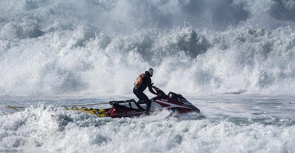 2 men riding on red and black kayak on sea during daytime