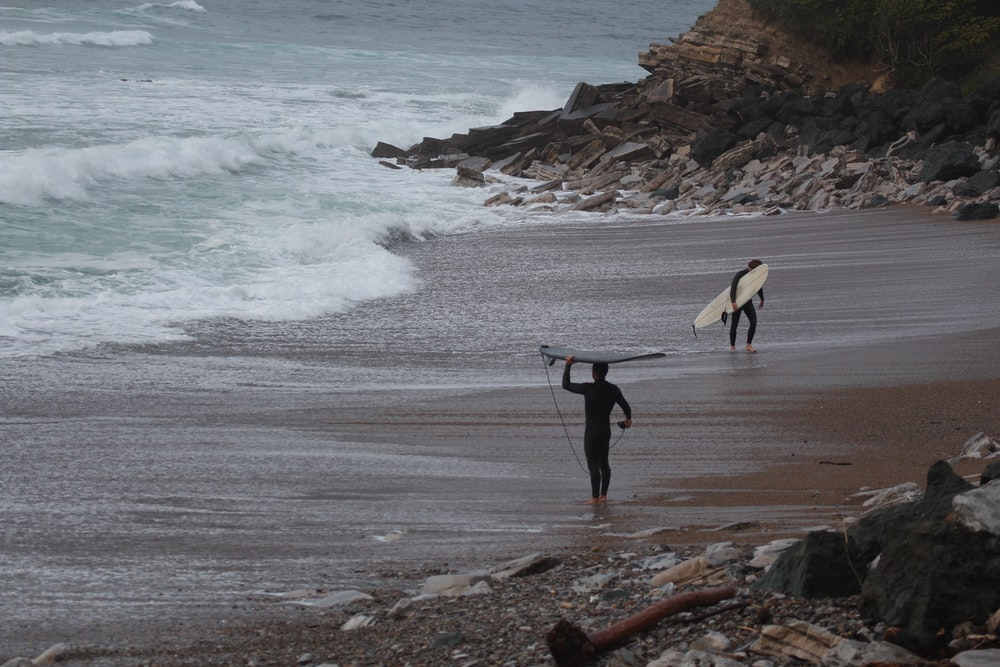 2 person holding surfboard walking on seashore during daytime