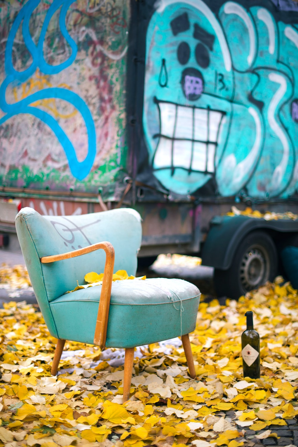 yellow and brown wooden chair beside blue and white graffiti wall