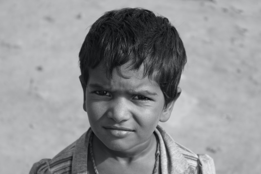 grayscale photo of boy in collared shirt