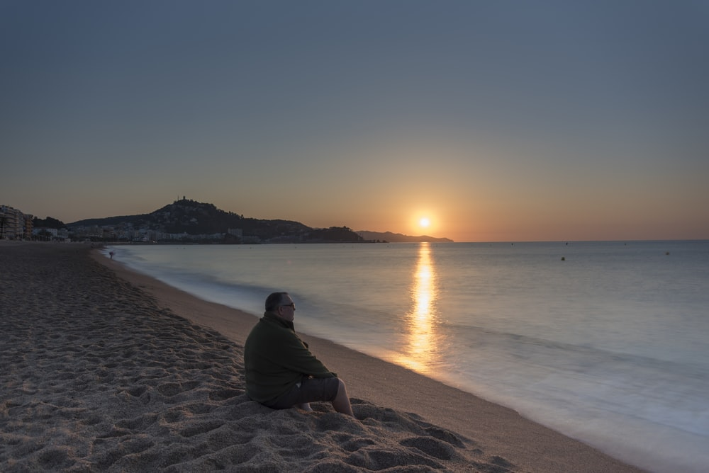 man in black hoodie sitting on brown sand near body of water during sunset