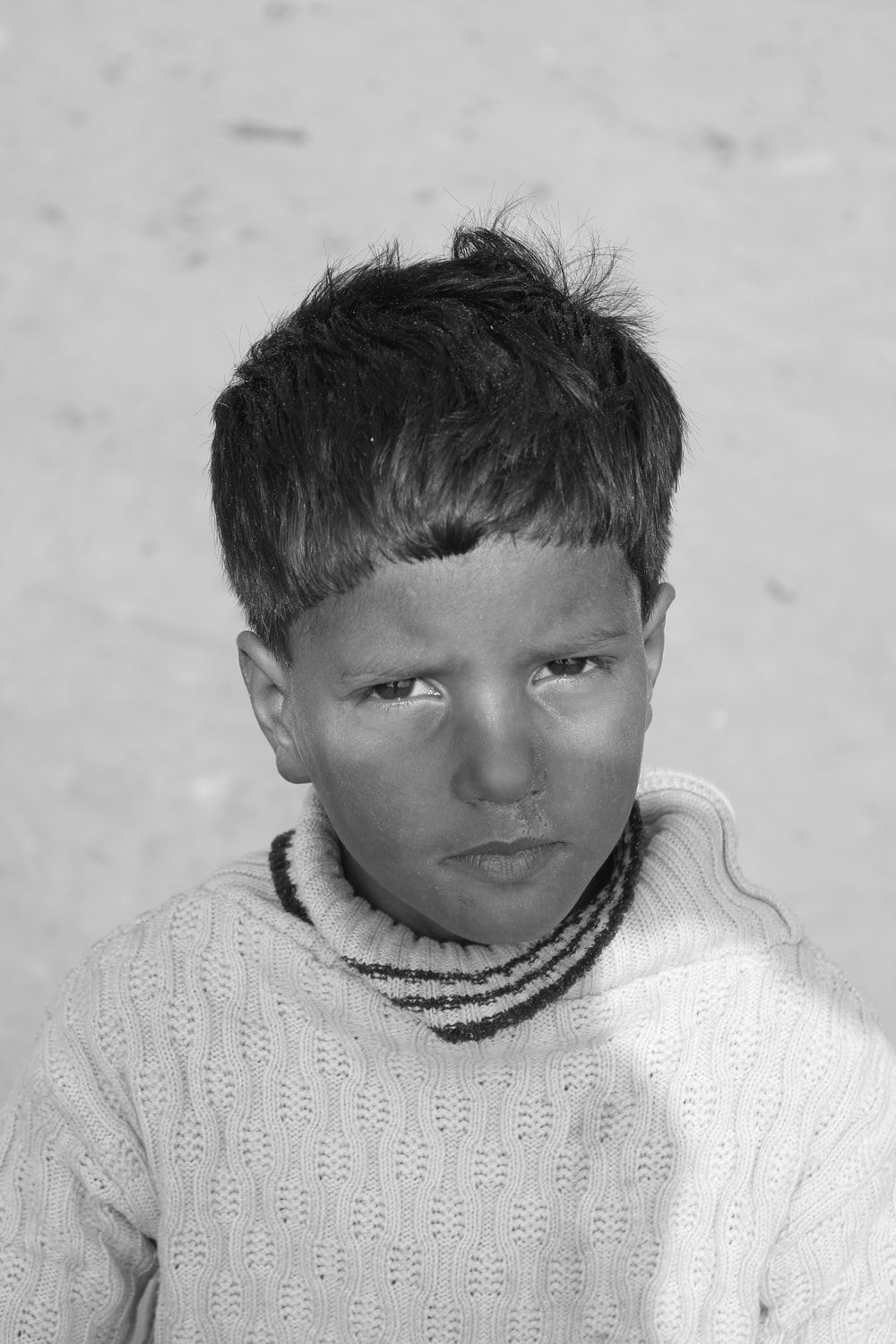 grayscale photo of boy in knit sweater