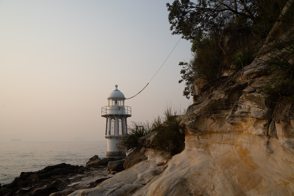 white and black lighthouse on brown rocky mountain near body of water during daytime