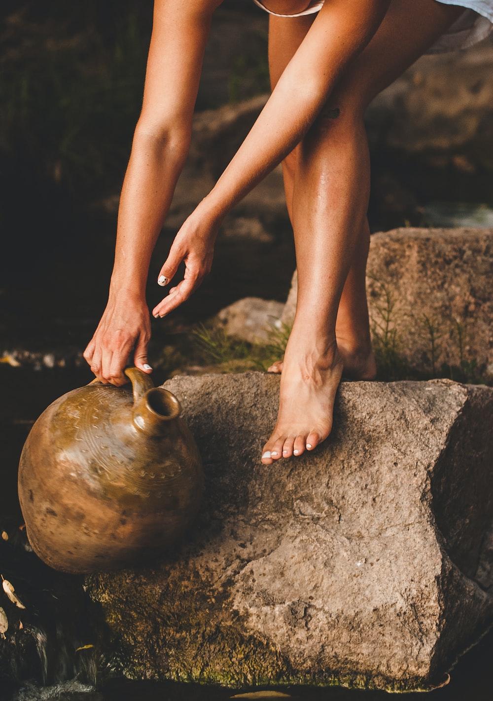 woman in black panty sitting on brown rock
