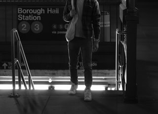 man in suit jacket standing beside street light in grayscale photography