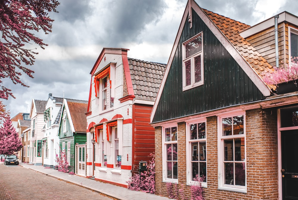 red white and black houses under white clouds during daytime