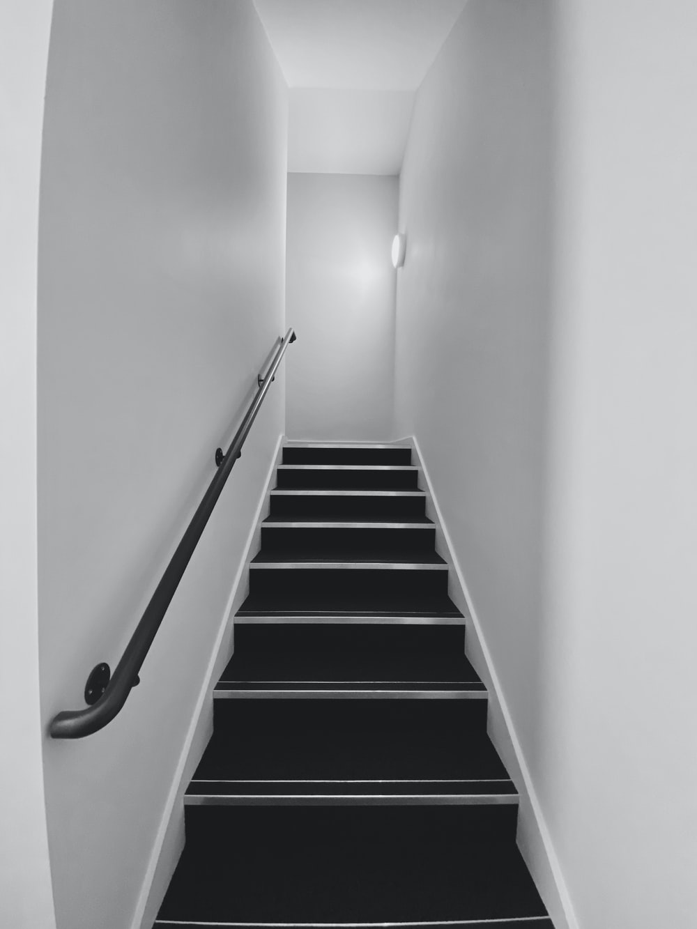 black and white staircase with stainless steel railings