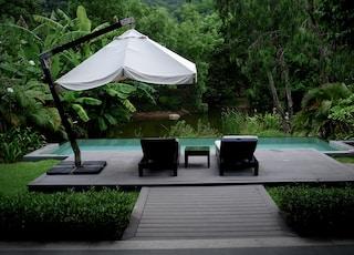 white patio umbrella near swimming pool