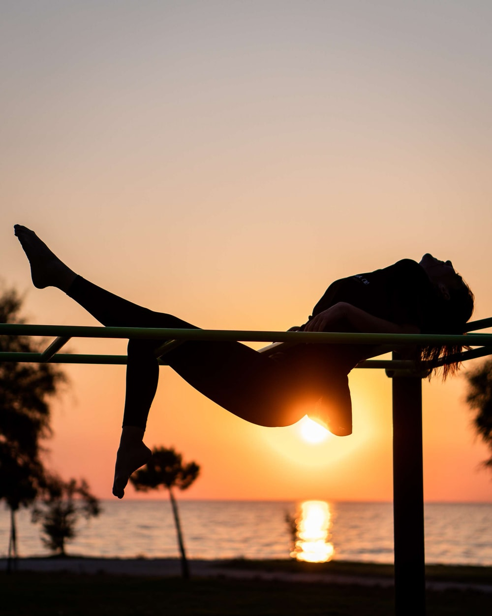 silhouette of woman doing yoga during sunset