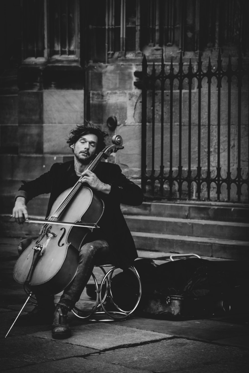 man playing violin on street in grayscale photography