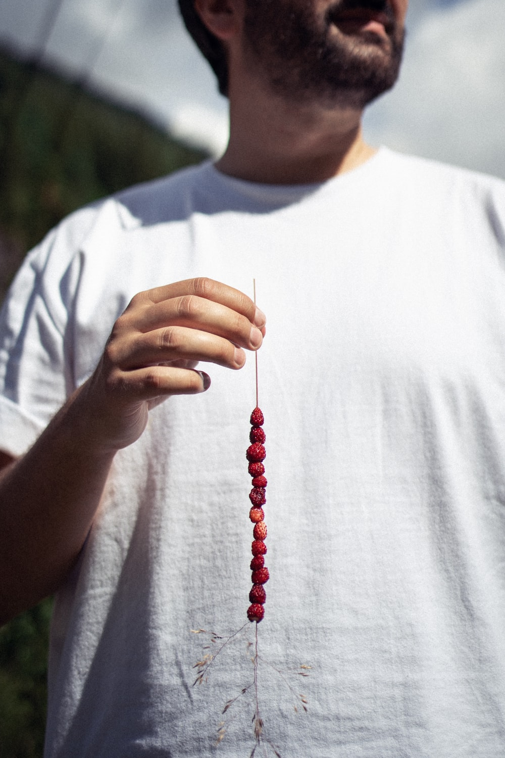 man in white crew neck t-shirt holding red beaded necklace