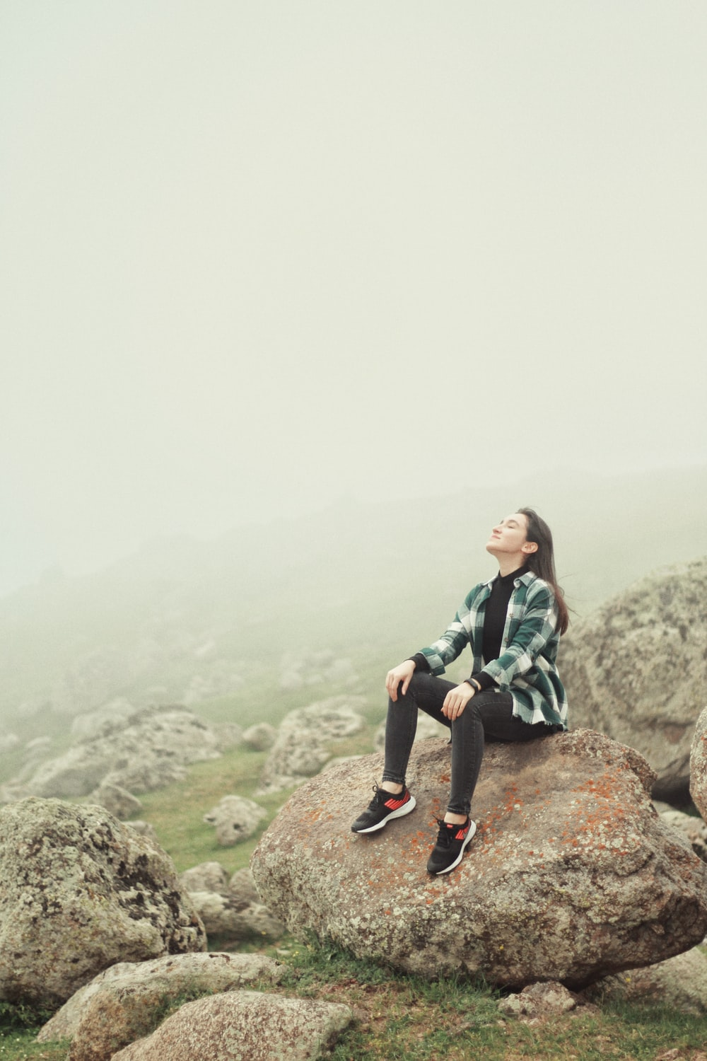 woman in green and black plaid shirt sitting on rock
