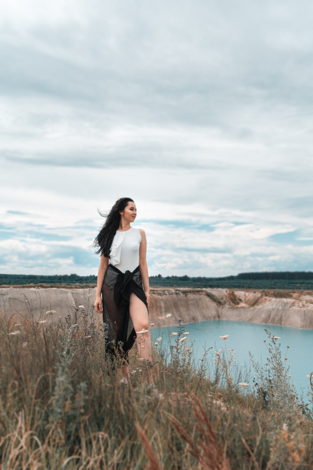 woman in black tank top standing on brown grass field near lake during daytime