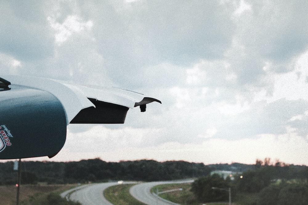 black plane flying over green grass field during daytime
