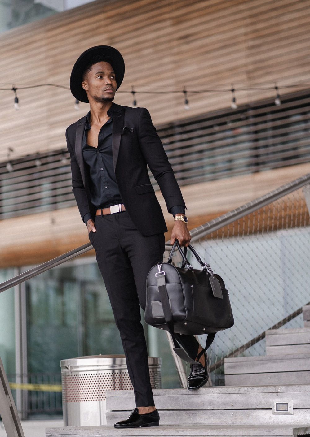 woman in black blazer and black pants with black leather shoulder bag standing on stairs