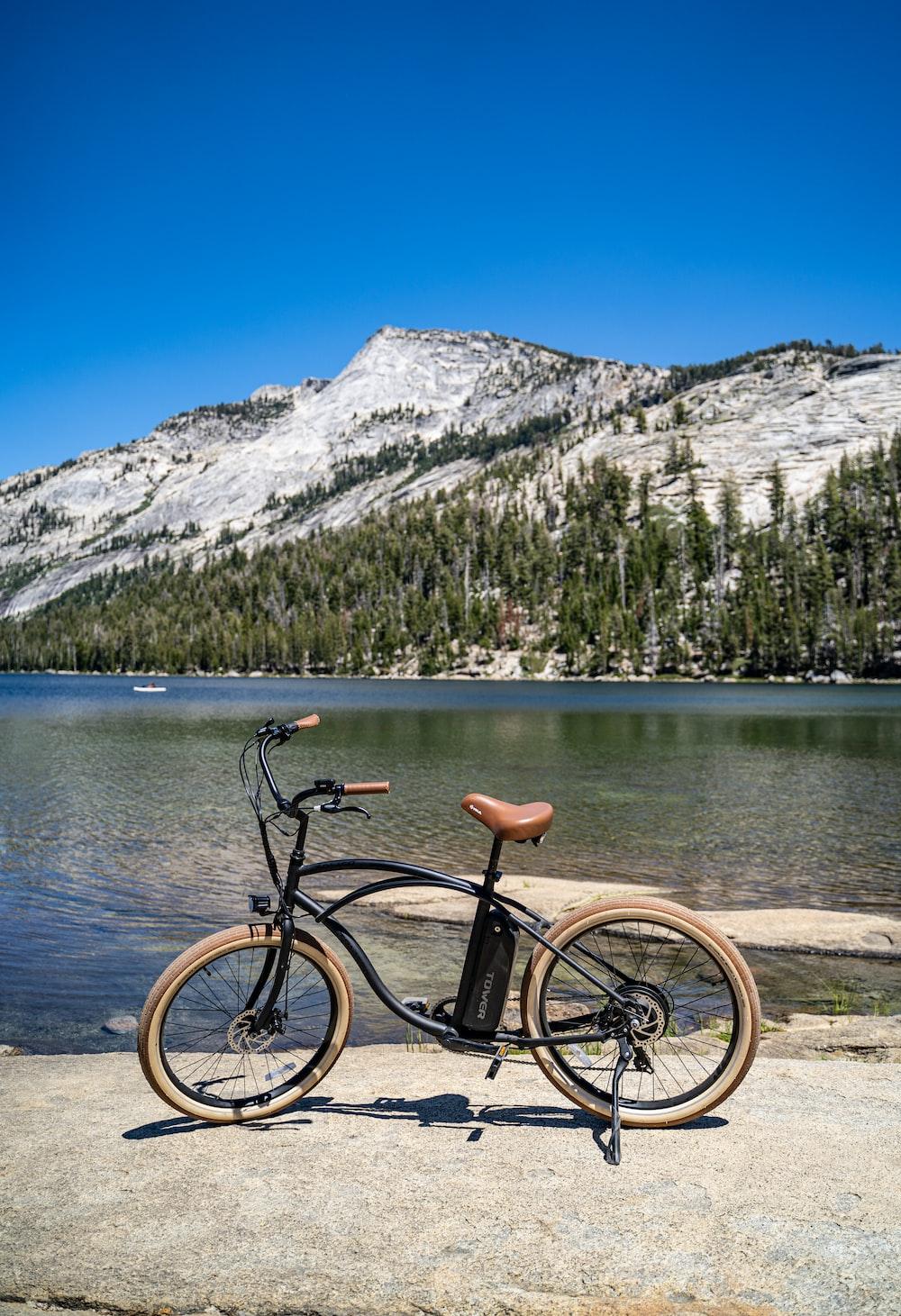 black bicycle on brown wooden dock near lake during daytime