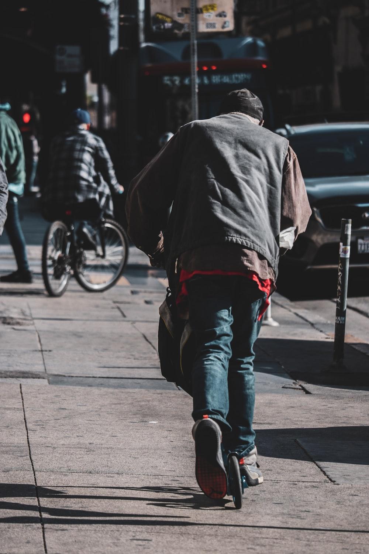 man in black jacket and blue denim jeans walking on sidewalk during daytime