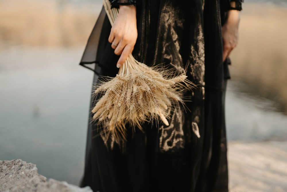 woman in black long sleeve dress holding brown dried grass