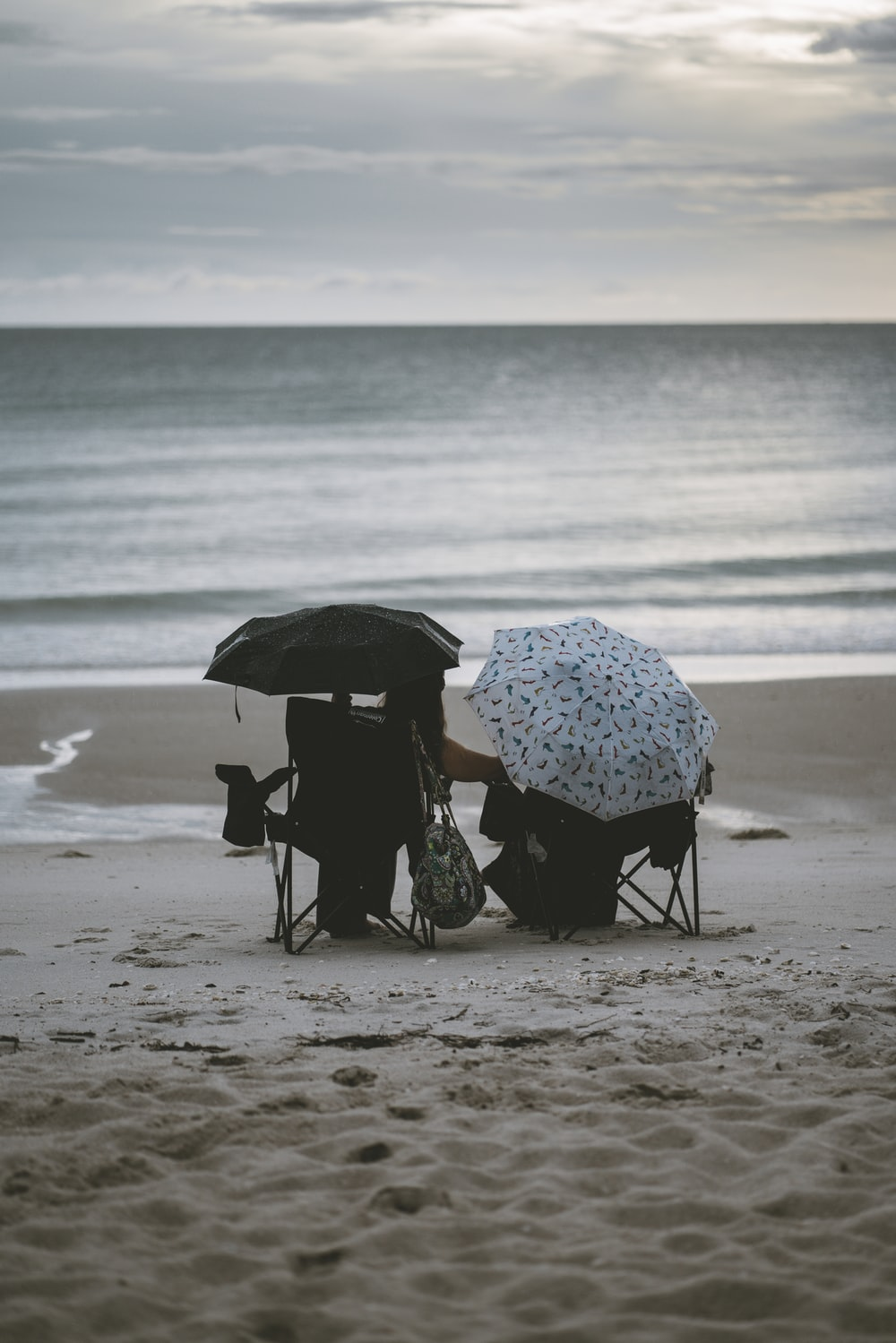 person holding umbrella walking on beach during daytime