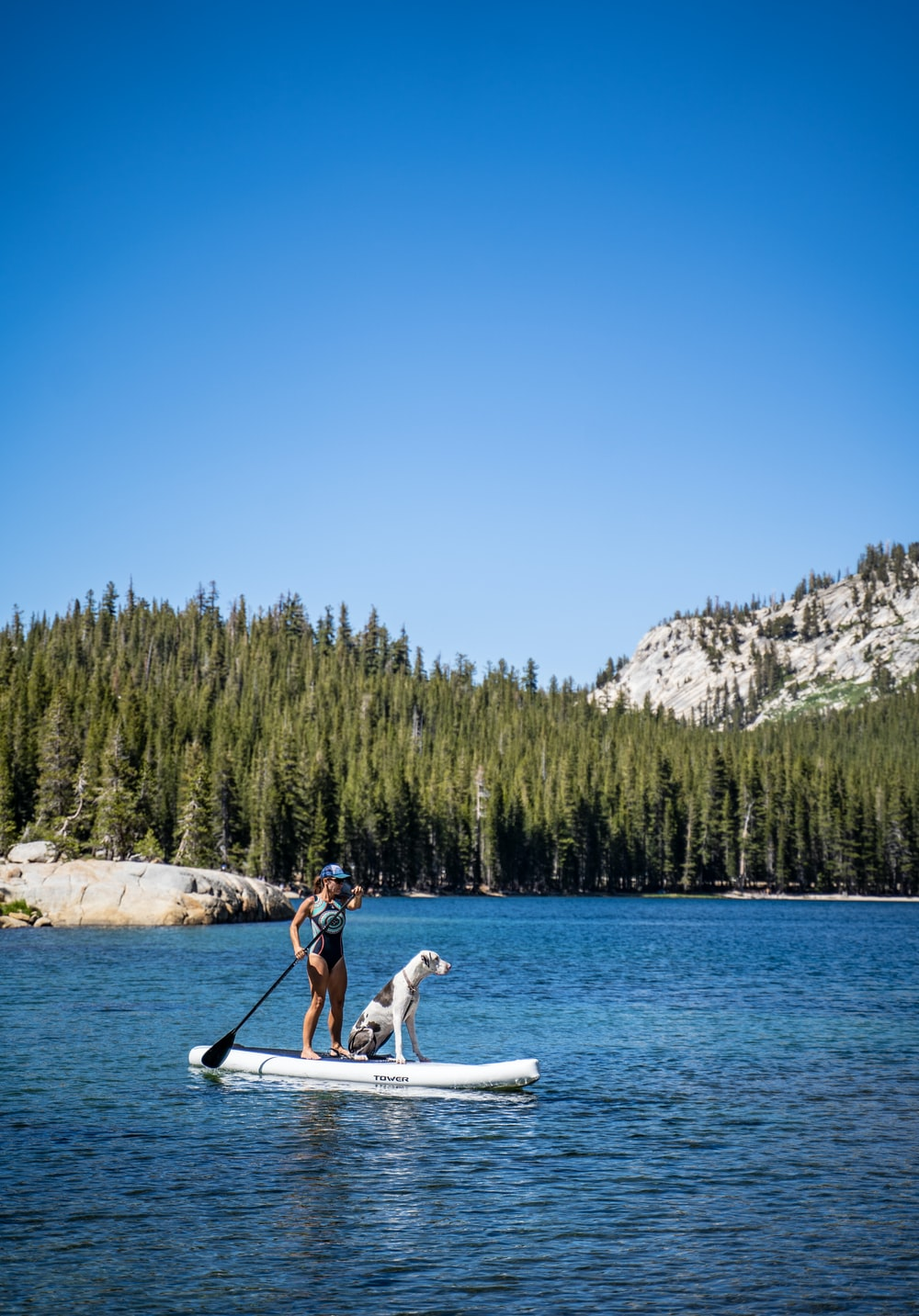 man and woman riding on white boat on lake during daytime