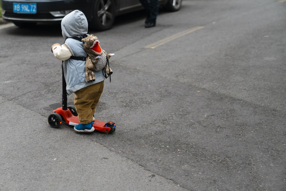child in brown jacket riding red kick scooter on gray asphalt road during daytime