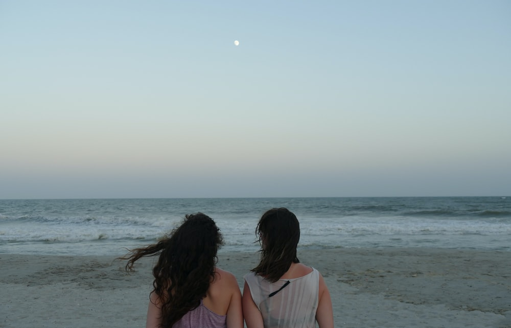 2 women in white tank top sitting on beach during daytime