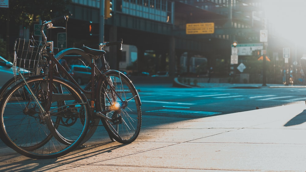 black bicycle parked beside road during daytime