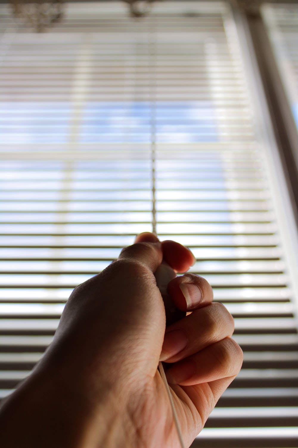 persons left hand near window blinds