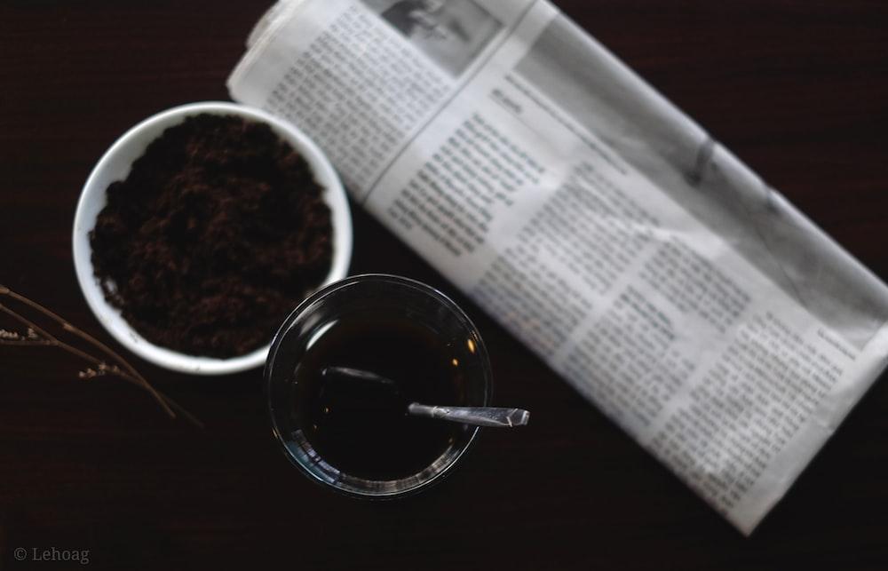 black liquid in clear glass mug on white paper