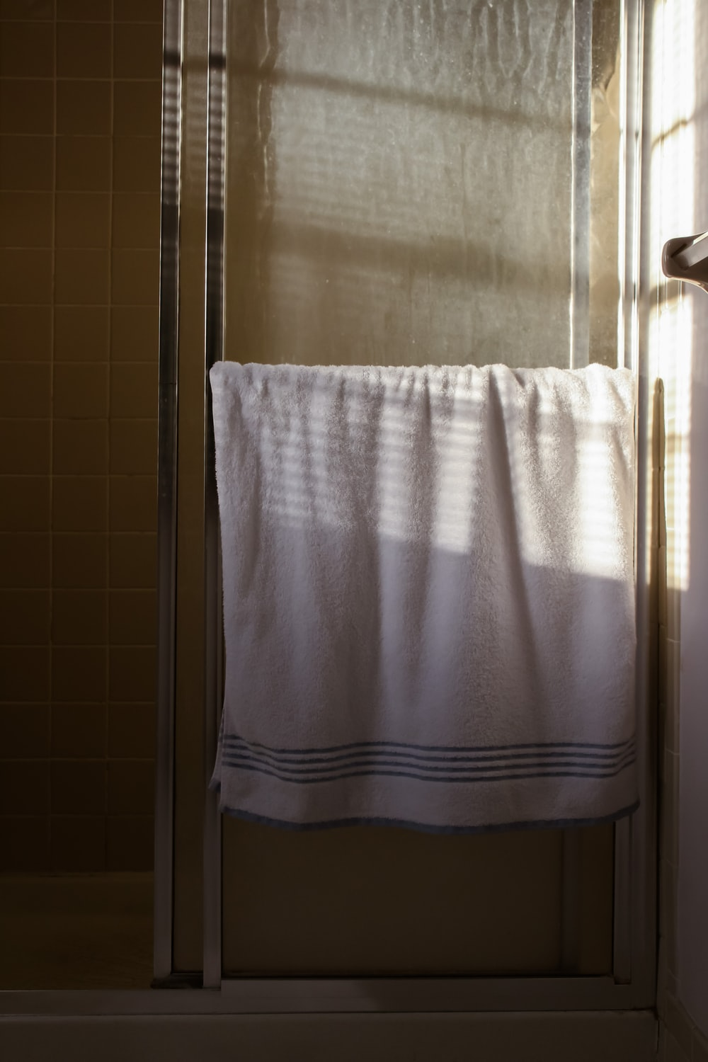 white towel on stainless steel towel bar