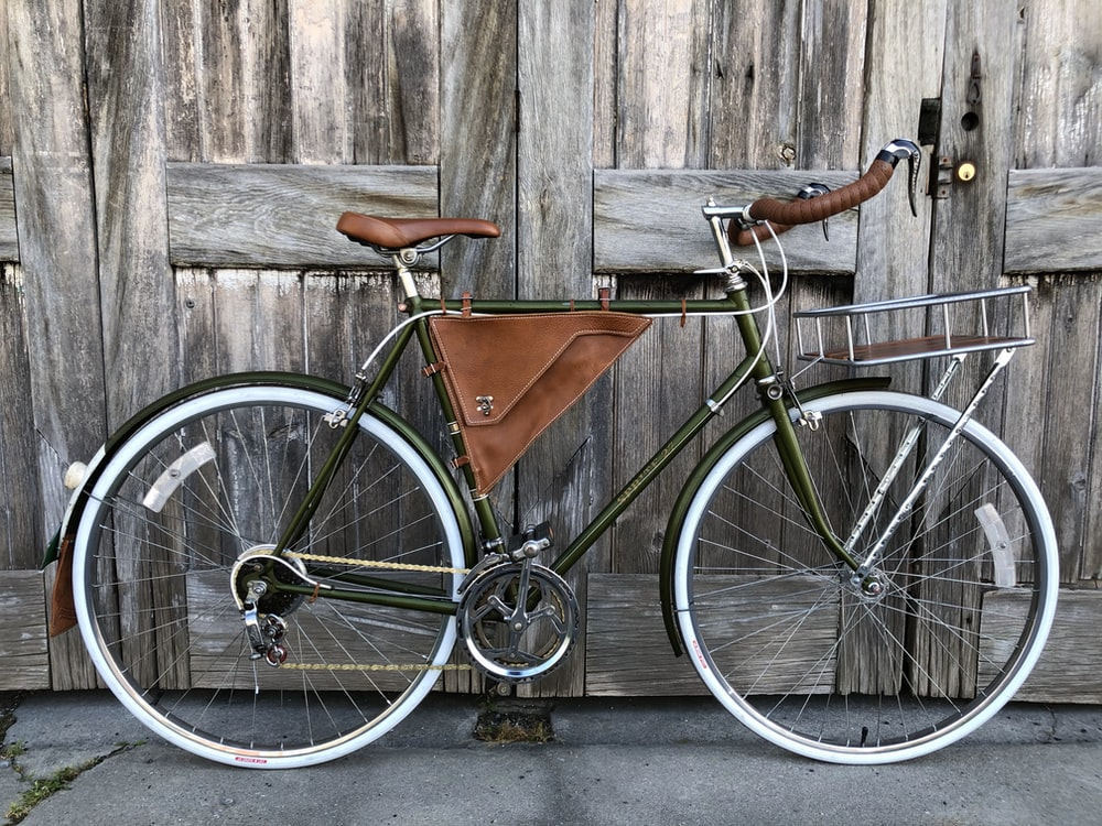 black and brown road bike leaning on brown wooden wall