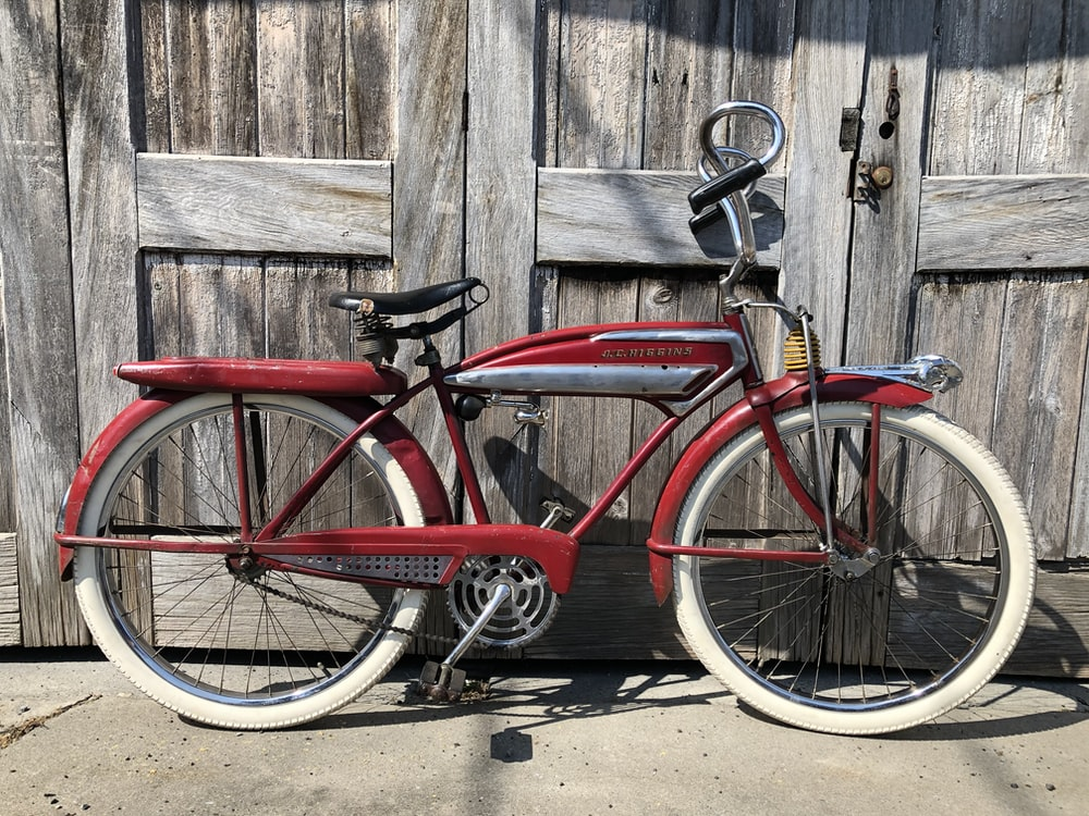 red city bicycle leaning on brown wooden wall