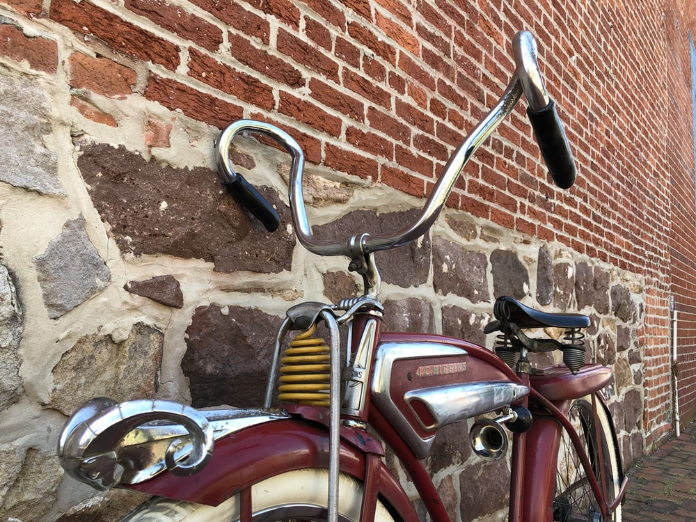 red and silver bicycle beside brown brick wall