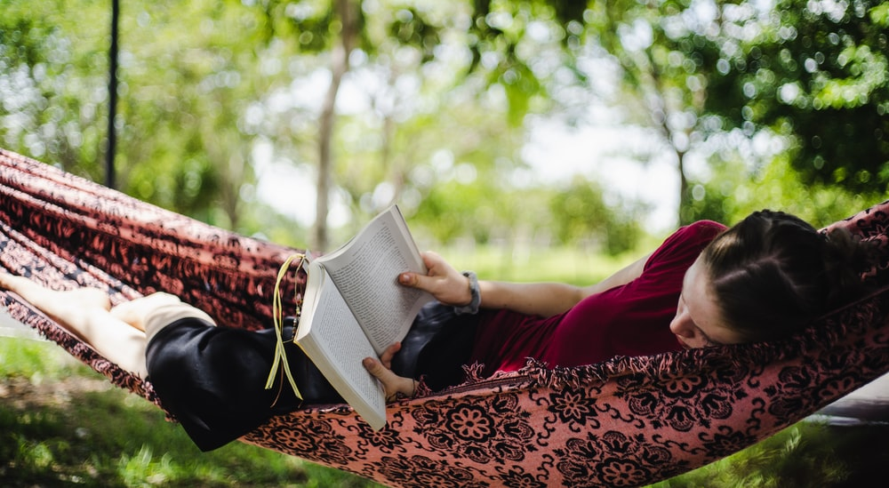 person in red long sleeve shirt reading book