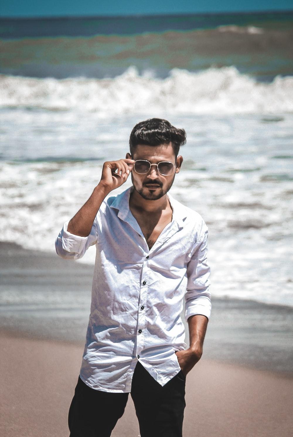man in white dress shirt wearing black sunglasses standing on beach during daytime