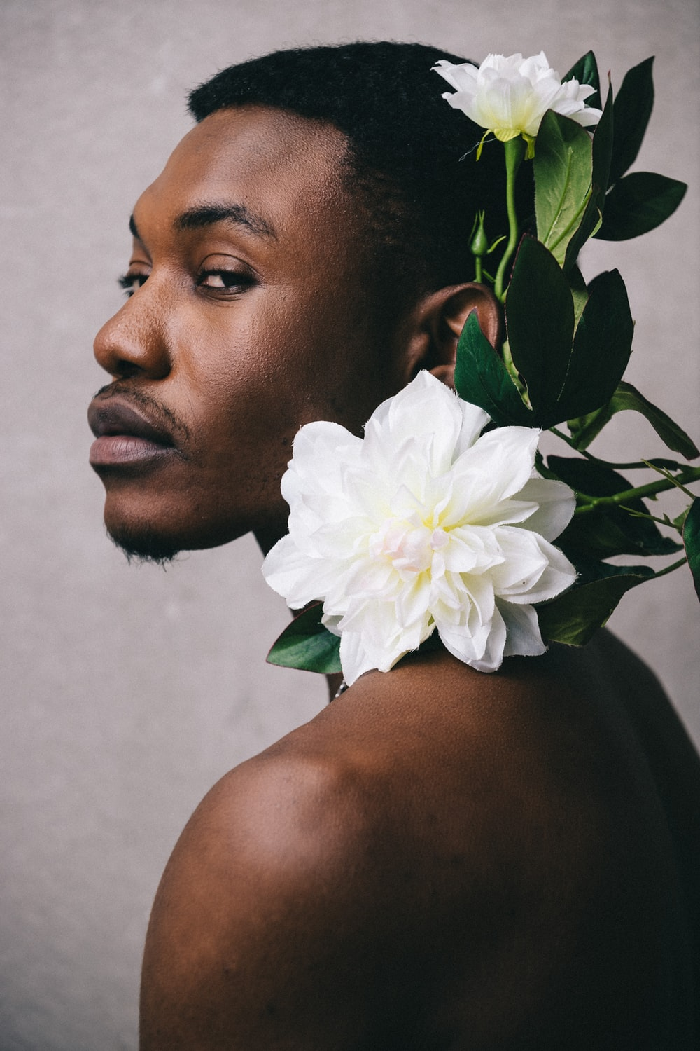 man with white flower on his ear