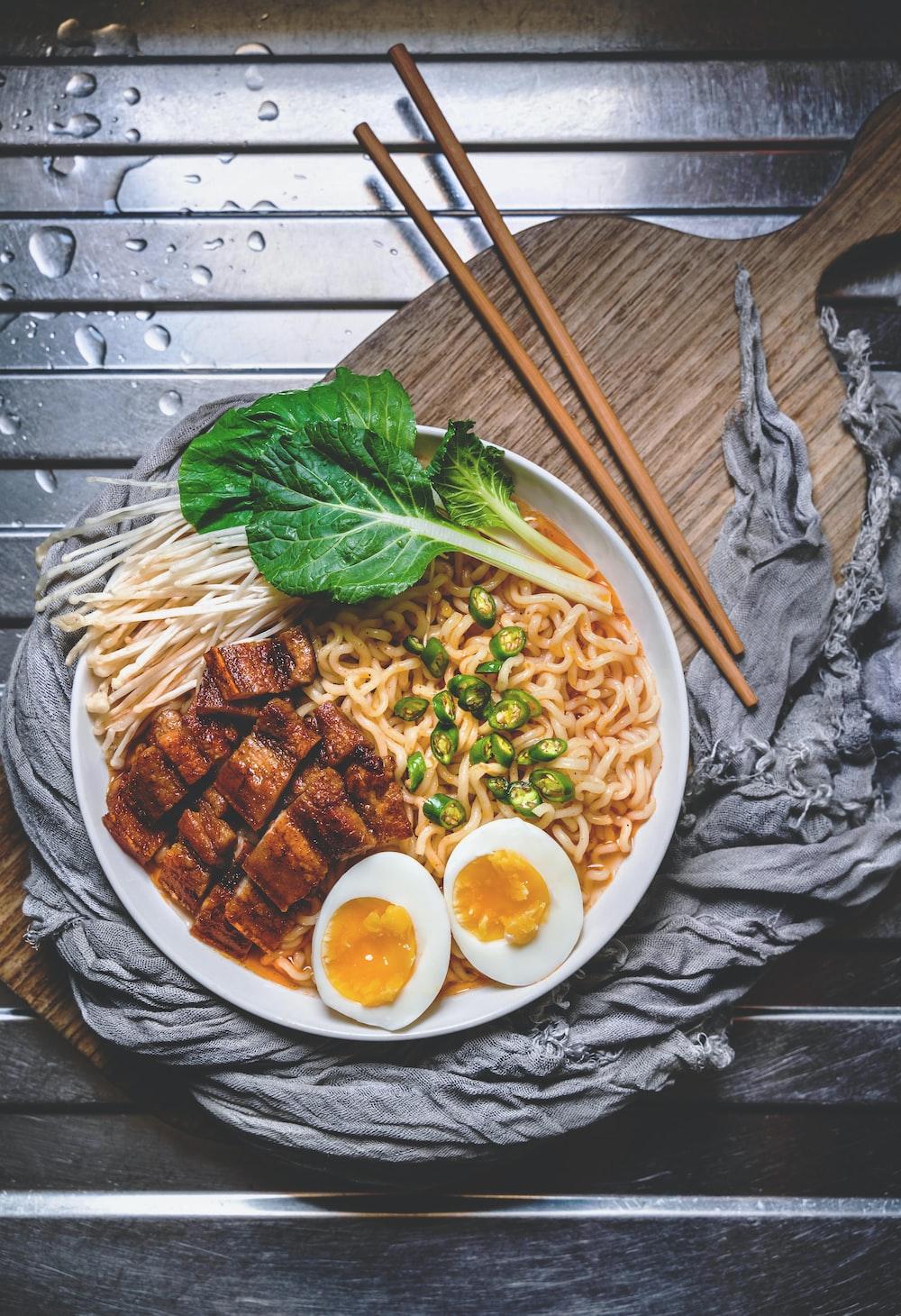white ceramic bowl with brown wooden chopsticks