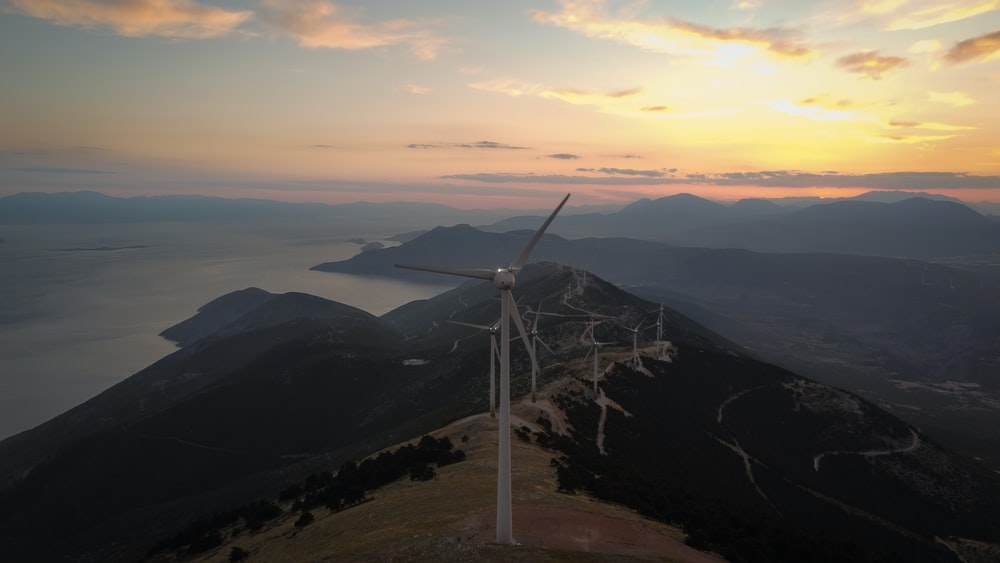 white wind turbine on top of mountain during daytime