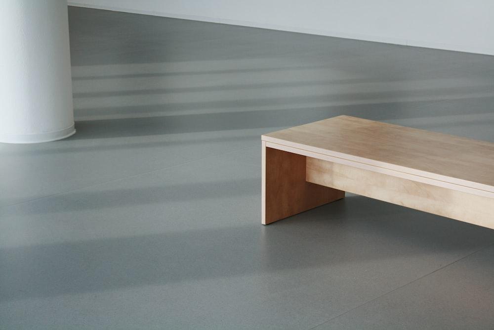 brown wooden table on gray floor