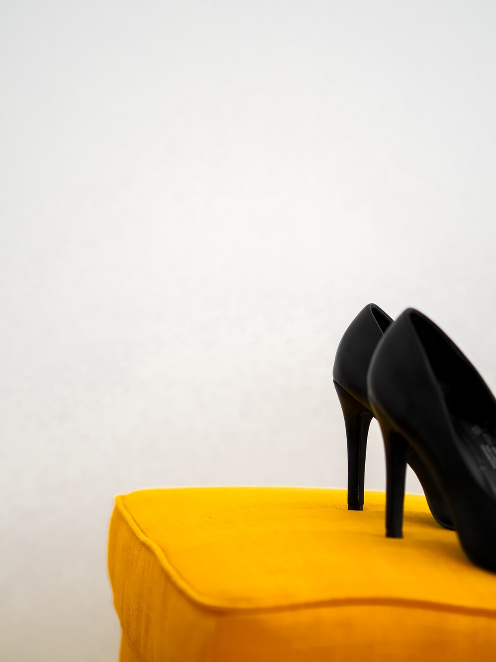 black leather heeled shoes on yellow chair