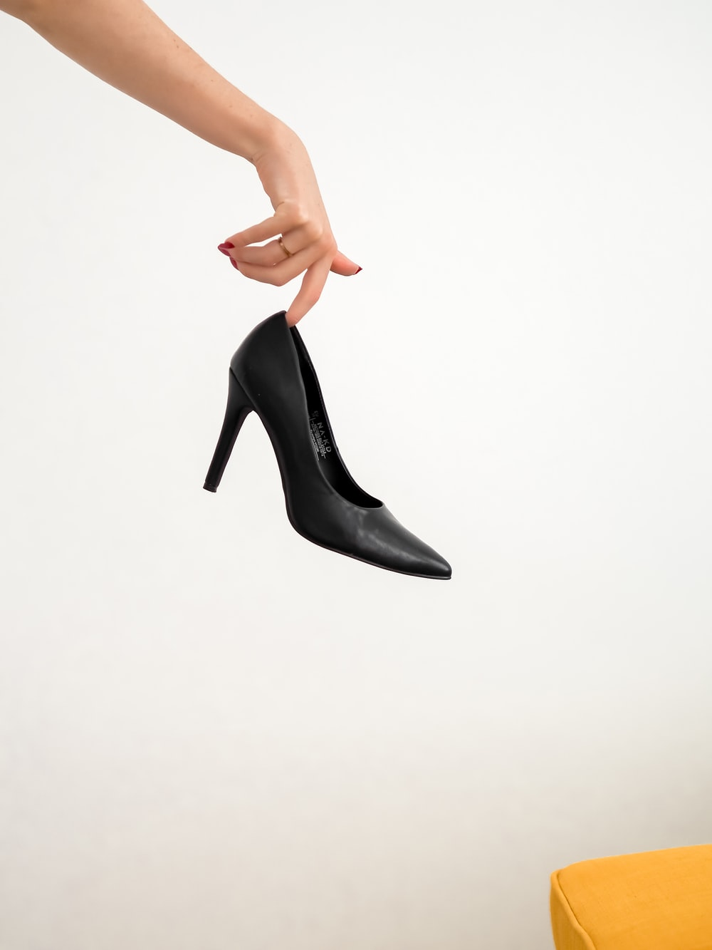 woman in black leather heeled shoes