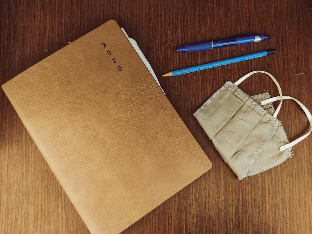 brown paper bag beside blue and white click pen
