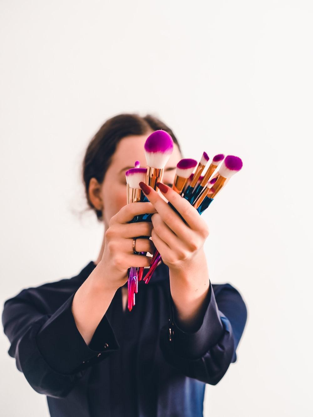 woman in black jacket holding makeup brush